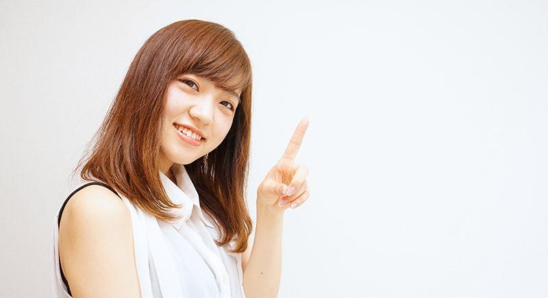 笑顔で指をさす若い女性 日本人 ポイント 指差
